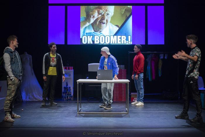 """lauréat label 2021 in solidum les 5 comédiens sont debout sur le plateau avec un écran qui projette une image d'une personne âge qui dit """" ok boomer"""""""